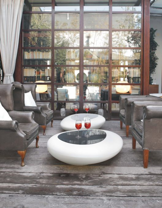 Grandfather leather armchairs with sleek plastic Kos coffee tables by Tonin Casa